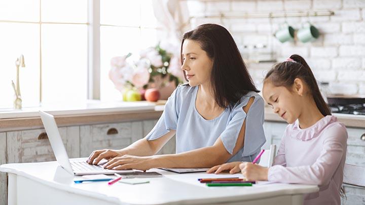 Mutter arbeitet am Laptop im Homeoffice während Tochter Hausaufgaben macht
